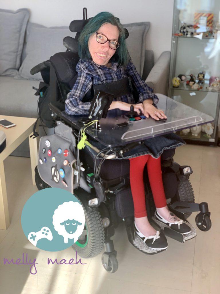 Melly lächelt in die Kamera. Sie trägt eine blaue, karrierte Bluse, einen Jeansrock und eine rote Leggins. Sie sitzt in einem elektrischen Rollstuhl.