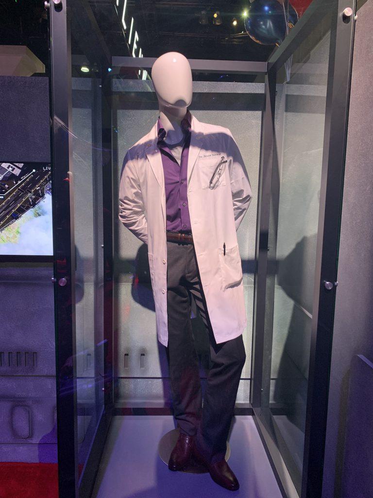 Das Kostüm von Bruce Banner besteht aus einem Labor-Kittel über einem lila Hemd und einer schwarzen Hose.