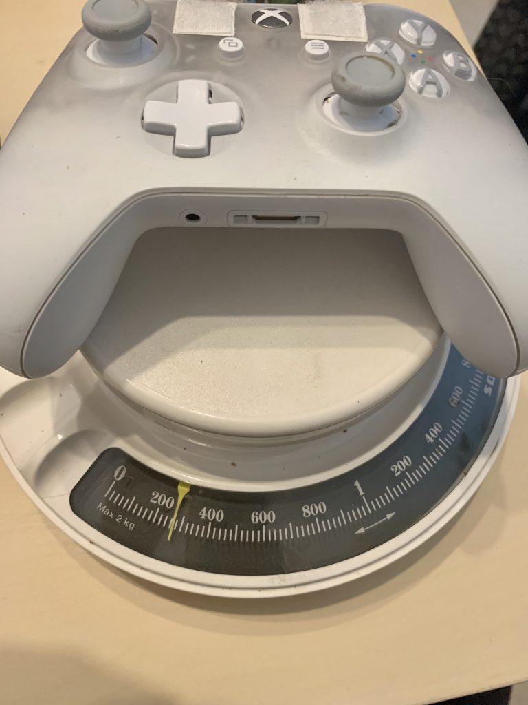 Der normale Controller liegt auf einer analogen Waage. Sie zeigt etwa 260 Gramm an.