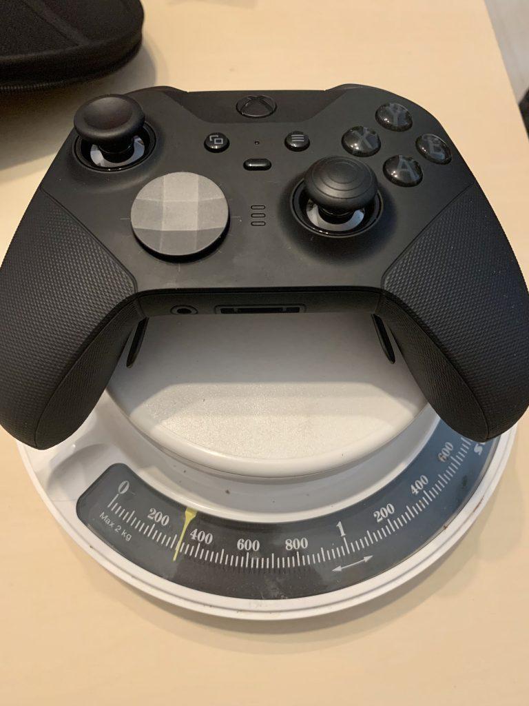 Der Elite Controller liegt auf einer analogen Waage. Sie zeigt etwa 320 Gramm an.