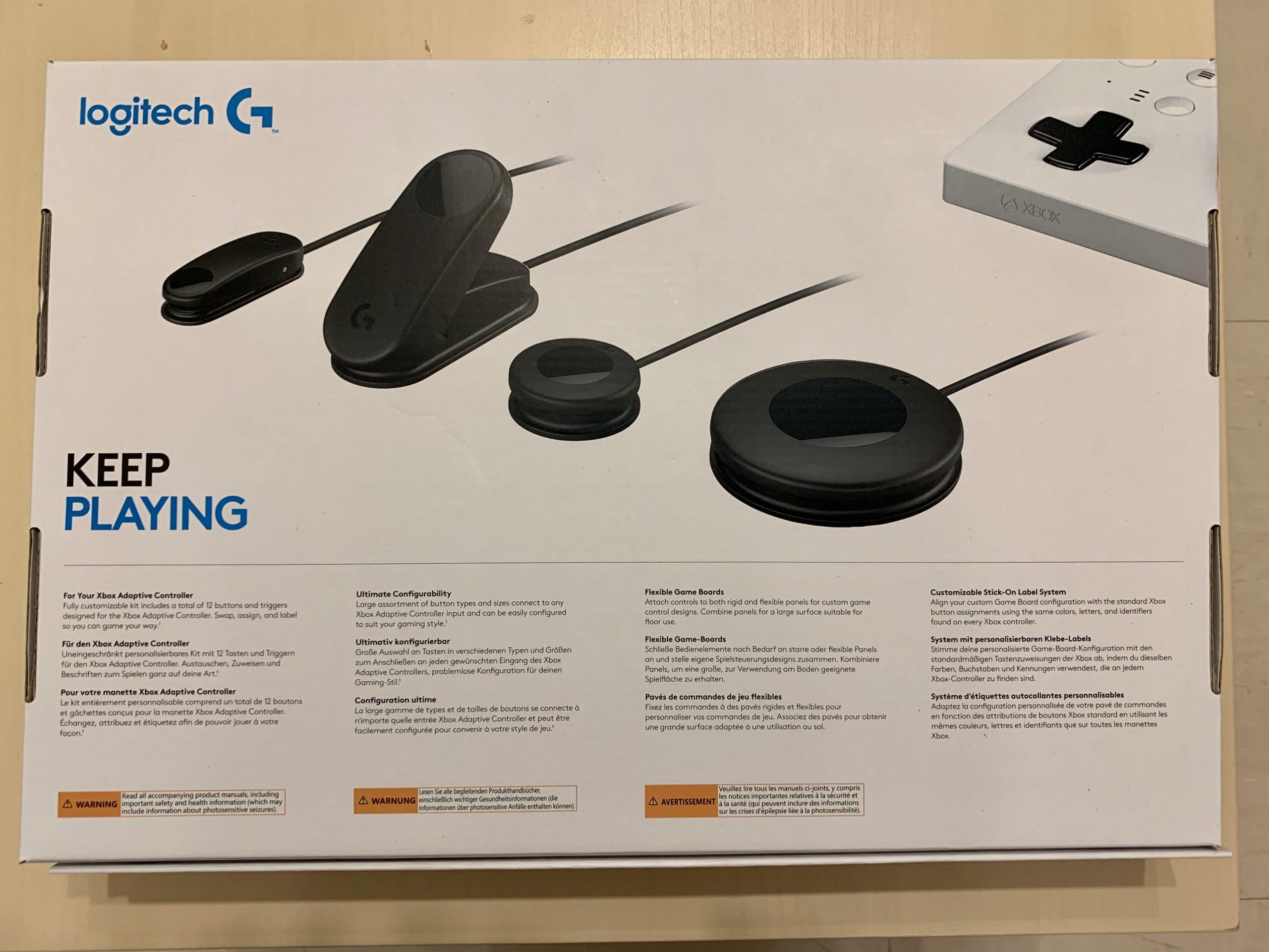 """Die Rückseite der Verpackung von Logitech Adaptive Gaming Kit. Jede einzelne Art von Knöpfen ist abgebildet und es steht der Slogan """"Keep Playing"""" daneben."""