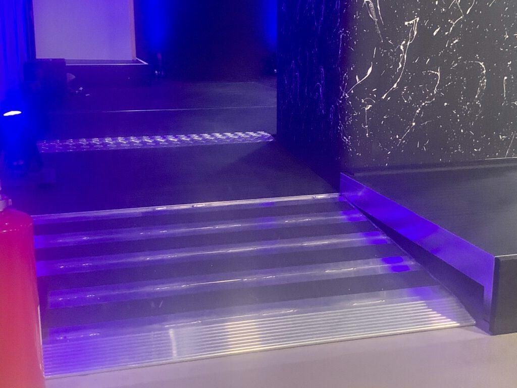 Eine Rampe führt neben einer kleinen Stufe auf eine Bühne.